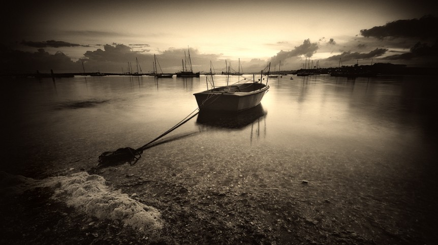 Long exposure waterscape photography in the Alvor, in the Algarve region, depicting a lonely boat, made by landscape photographer José Ramos from Portugal