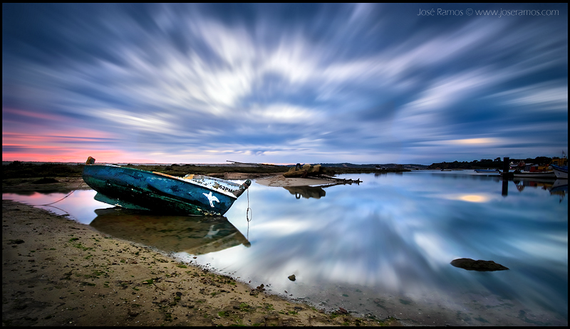 Long exposure waterscape photography in Alvor, in the Algarve region, depicting a lonely boat, made by landscape photographer José Ramos from Portugal