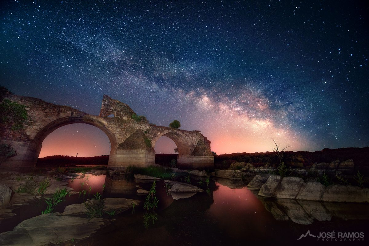 Long exposure night photography showing the Milky Way above the ancient bridge of Ajuda in Elvas, Portugal, near the border with Spain